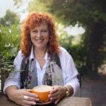 Lynn Moresi sitting with orange coffee cup